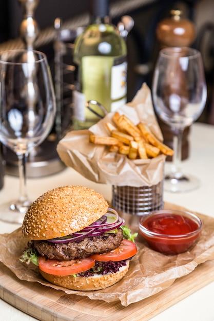 Piatto di servizio del ristorante - hamburger con la cotoletta con la patata fritta sul bordo di legno Foto Premium