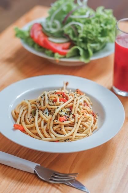 Piatto di spaghetti con verdure wok e insalata fresca in un ristorante. avvicinamento. Foto Premium
