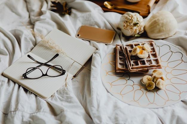Piatto di waffle colazione con guarnizione di banana su un letto bianco accanto a un diario e un telefono Foto Gratuite