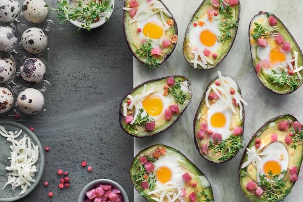 Piatto dietetico keto: avocado con cubetti di prosciutto, uova di quaglia, formaggio e germogli di crescione Foto Premium