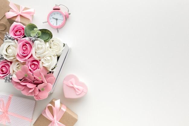 Piatto disteso di rose in scatola con orologio e regali Foto Gratuite