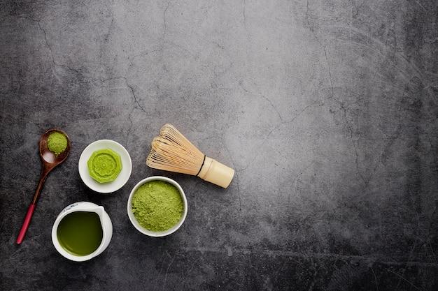 Piatto disteso di tè matcha con cucchiaio di legno Foto Gratuite