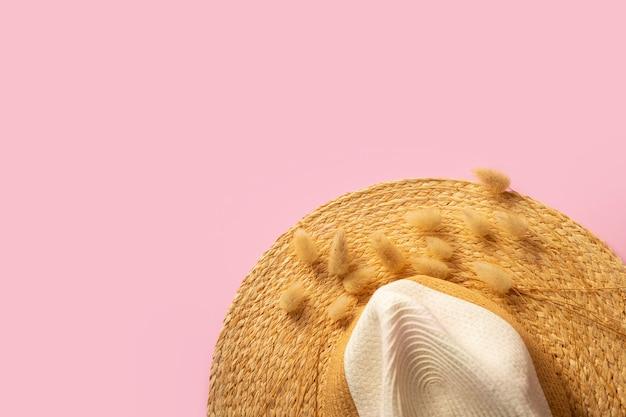 Piatto giaceva con cappello di paglia color sabbia ed erba secca di coniglietto su sfondo rosa. accessorio femminile. concetto di vacanza viaggio estivo. copia spazio. armonia e unione con la natura. vita ecologica Foto Premium