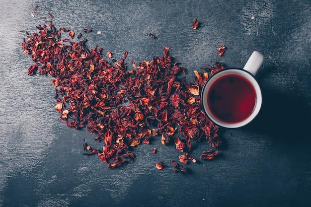 Piatto giaceva una tazza di tè con erbe aromatiche su sfondo scuro con texture. orizzontale Foto Gratuite