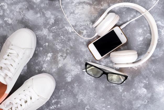 Piatto laici di scarpe da tennis bianche su sfondo di pietra con telefono e cuffie. Foto Premium