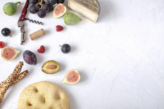 Piatto lay antipasto di vino fico prosciutto uva prugna formaggio focaccia grissini Foto Premium