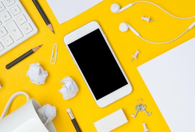Piatto lay di area di lavoro desktop con display dello smartphone spazio vuoto su sfondo giallo Foto Premium