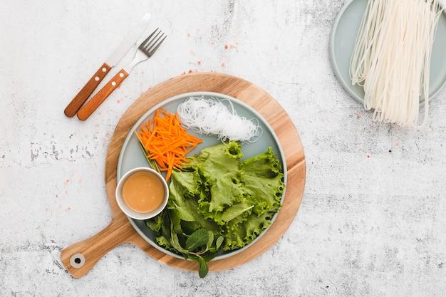 Piatto lay di piatto di verdure fresche e noodles Foto Gratuite