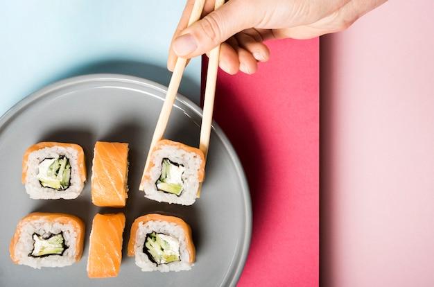 Piatto minimalista con involtini di sushi e bacchette Foto Gratuite