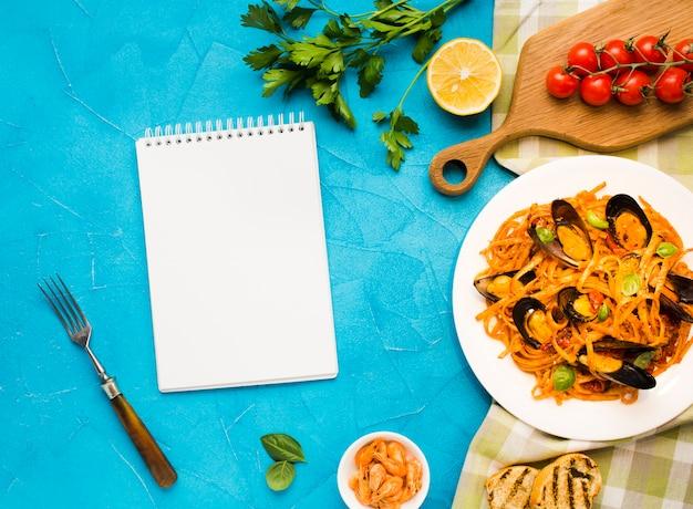 Piatto piano di pasta di cozze con notebook Foto Gratuite