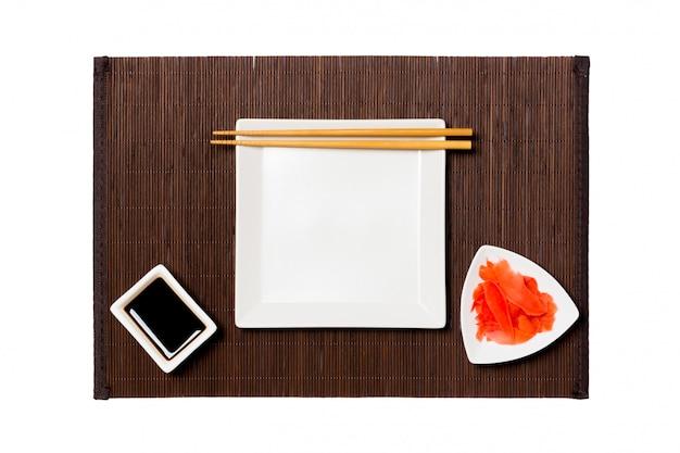 Piatto quadrato bianco vuoto con le bacchette per salsa di sushi, zenzero e soia sulla stuoia di bambù scuro. Foto Premium