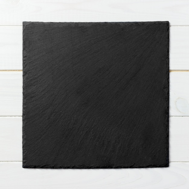 Piatto quadrato nero su fondo in legno Foto Premium