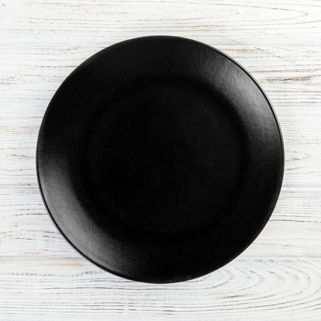 Piatto rotondo nero su fondo di legno, vista dall'alto, spazio di copia Foto Premium