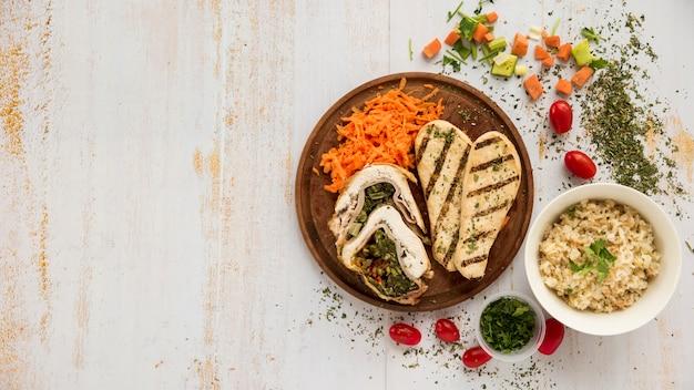 Piatto sano con pollo e verdure sullo scrittorio di legno del grunge Foto Gratuite