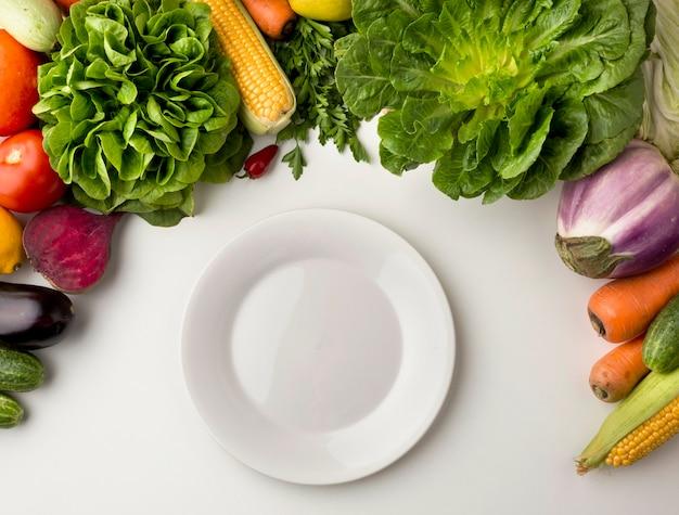 Piatto vuoto con disposizione vegetale Foto Gratuite