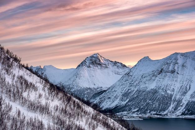 Picco di montagna innevato con cielo striscia colorata Foto Premium