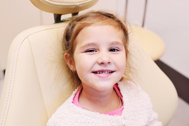 Piccola bambina con carie dentale sui denti nella sedia dentale sui denti nella poltrona del dentista Foto Premium