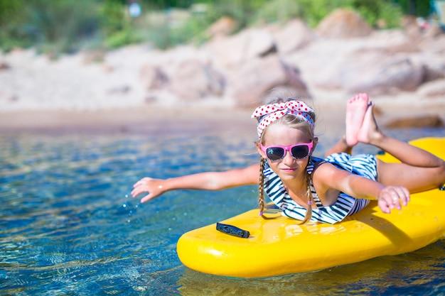Piccola bella ragazza sveglia che kayaking nel mare blu libero Foto Premium