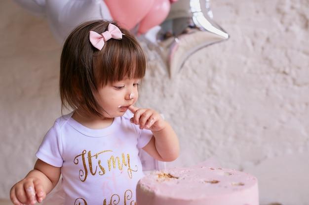 Piccola festa di compleanno affascinante bambino in abito rosa si siede sulla sedia Foto Gratuite