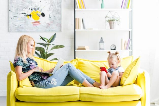 Piccola figlia che utilizza telefono cellulare mentre sua madre che lavora al computer portatile Foto Gratuite