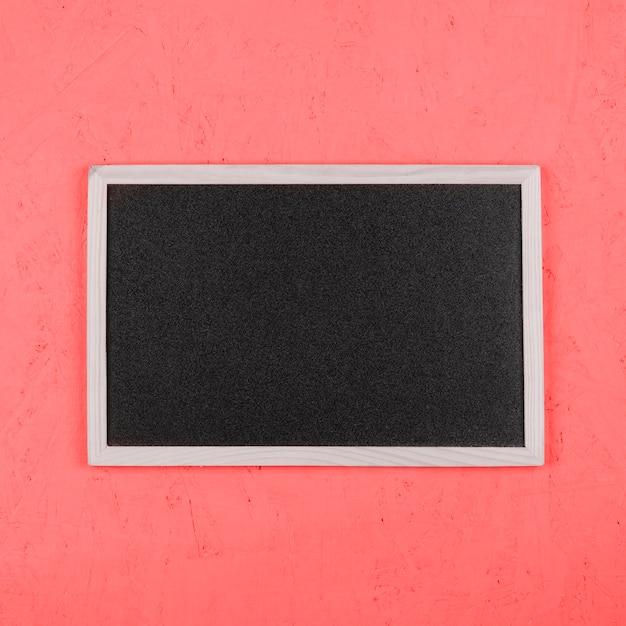 Piccola lavagna vuota sul muro dipinto di corallo Foto Gratuite