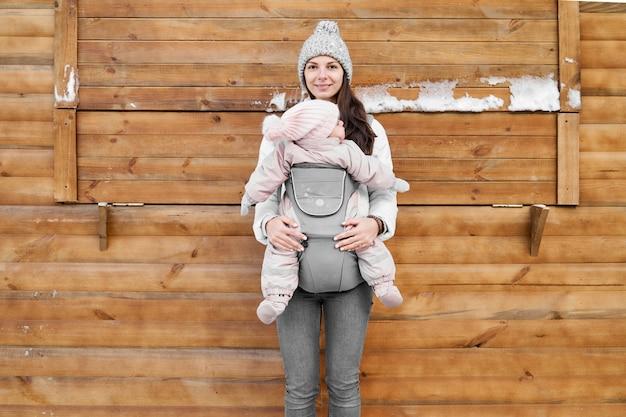 Piccola neonata e sua madre babywearing nel trasportatore di ergo nel fondo di legno di inverno Foto Premium
