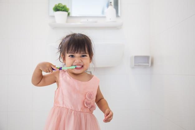 Piccola neonata sveglia che pulisce i suoi denti con lo spazzolino da denti nel bagno Foto Premium