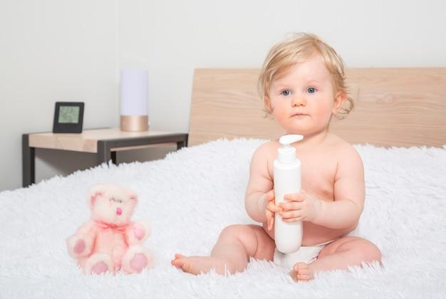 Piccola neonata sveglia con la bottiglia di olio per bambini nella camera da letto del genitore. Foto Premium