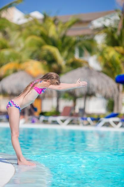 Piccola ragazza adorabile attiva nella piscina all'aperto pronta a nuotare Foto Premium