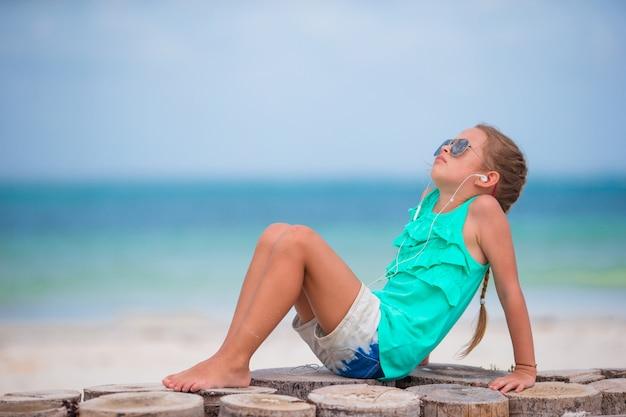 Piccola ragazza adorabile che ascolta la musica sulle cuffie sulla spiaggia Foto Premium