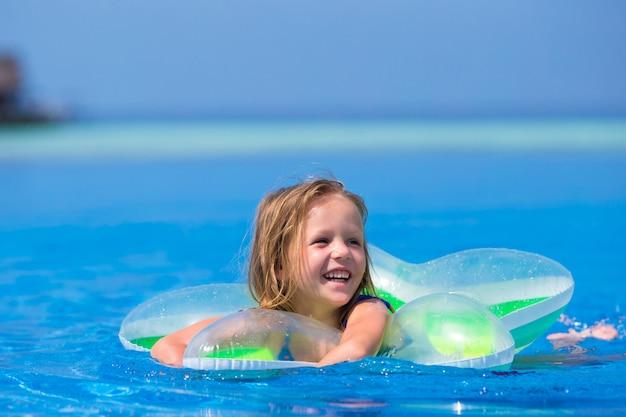 Piccola ragazza adorabile felice nella piscina all'aperto Foto Premium