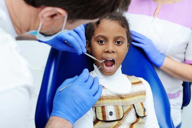 Piccola ragazza africana con la pelle scura in odontoiatria Foto Premium