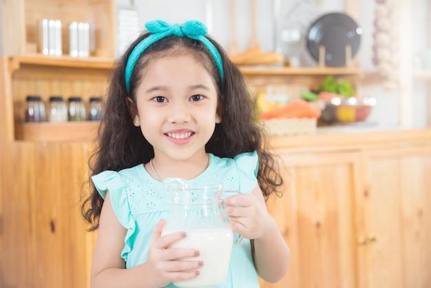 Piccola ragazza asiatica che tiene una brocca di latte e sorride in cucina Foto Premium