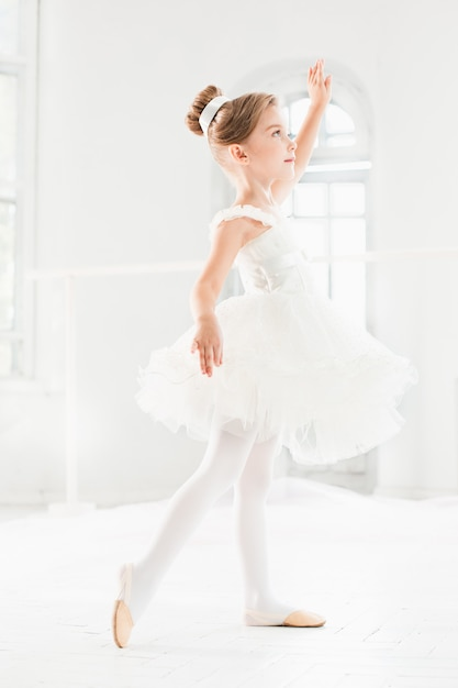 Piccola ragazza ballerina in un tutu. bambino adorabile che balla balletto classico in uno studio bianco. Foto Gratuite