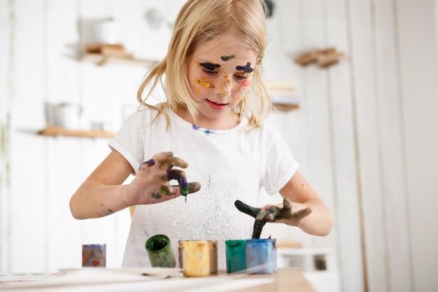 Piccola ragazza bionda che approfondisce le sue dita in pittura. una bambina europea occupata con la pittura, indossa una maglietta bianca con macchie di vernice sul viso. bambini e arte. Foto Gratuite