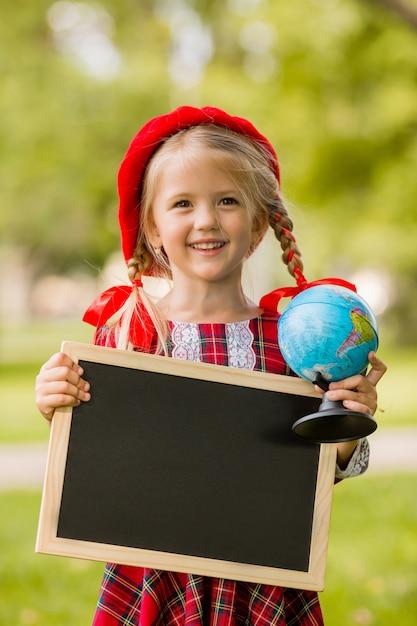 Piccola ragazza bionda di prima elementare in abito rosso e berretto in possesso di un tavolo da disegno vuoto e globo Foto Premium