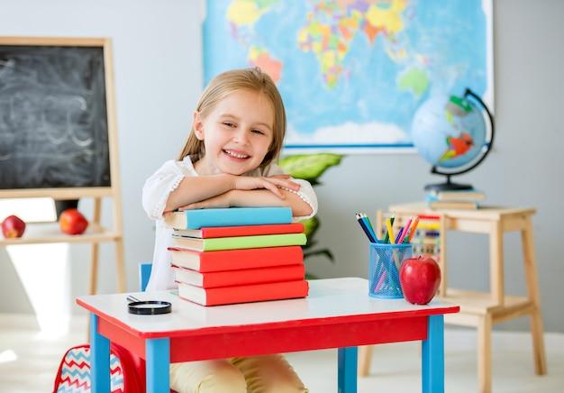 Piccola ragazza bionda sorridente che si tiene per mano sui libri nell'aula della scuola Foto Premium
