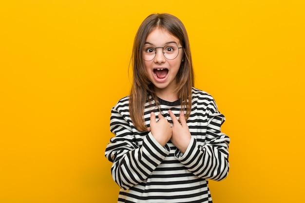 Piccola ragazza carina caucasica sorpresa indicando se stesso, sorridendo ampiamente. Foto Premium