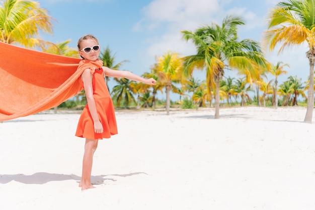Piccola ragazza del cutie che gioca supereroe ad una spiaggia tropicale Foto Premium