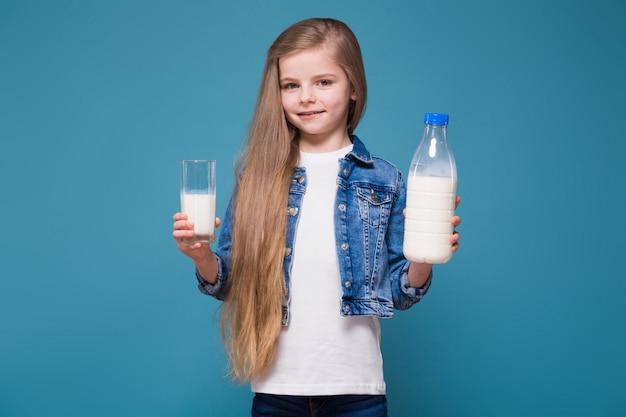 Piccola ragazza di bellezza in giacca di jeans con lunghi capelli castani tenere il contenitore del latte Foto Premium