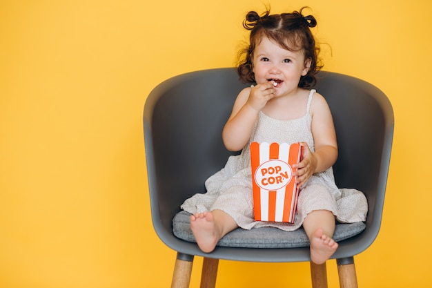 Piccola ragazza divertente che sorride e che si siede su una sedia a casa che mangia pop corn e che guarda un film Foto Premium
