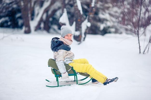 Piccola ragazza felice adorabile che sledding nel giorno nevoso di inverno. Foto Premium