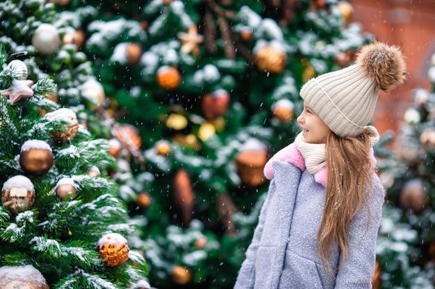 Piccola ragazza felice vicino al ramo dell'abete in neve per il nuovo anno. Foto Premium