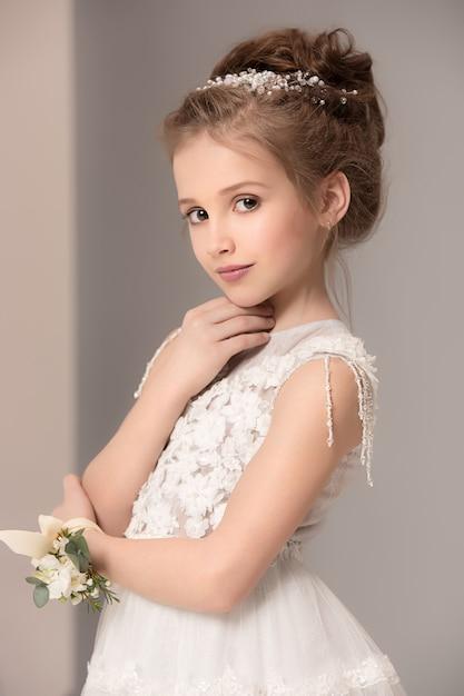 Piccola ragazza graziosa con i fiori vestiti in abiti da sposa Foto Gratuite