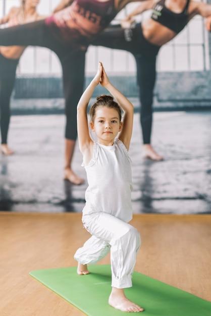 Piccola ragazza innocente che fa yoga in palestra Foto Gratuite