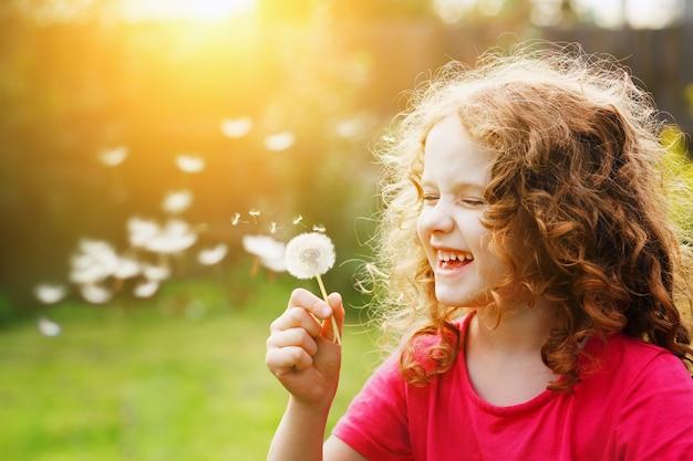 Piccola ragazza riccia che soffia il dente di leone e ridendo. Foto Premium