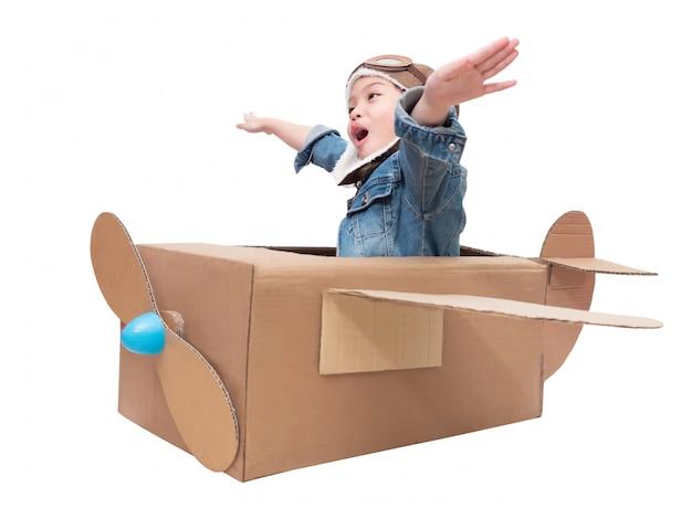 Piccola ragazza sveglia asiatica 6 anni che gioca l'aeroplano di cartone isolato su bianco con il percorso di ritaglio. bambino gioca come pilota su aeroplano di cartone fai-da-te. Foto Premium