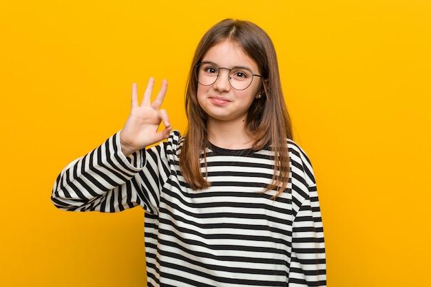 Piccola ragazza sveglia caucasica allegra e sicura che mostra gesto giusto. Foto Premium