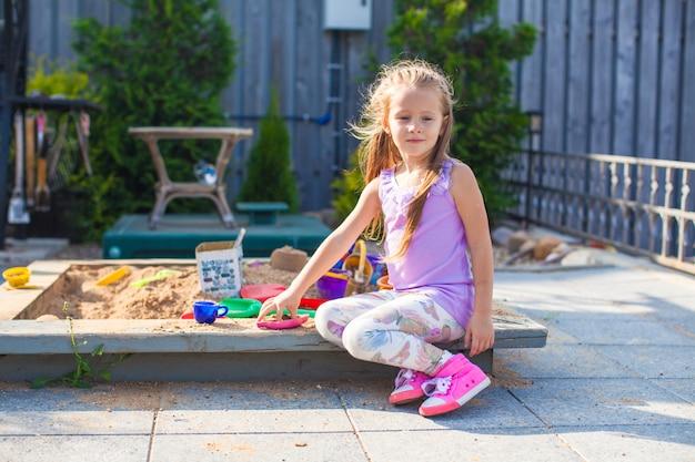 Piccola ragazza sveglia che gioca al sandbox con i giocattoli nell'iarda Foto Premium