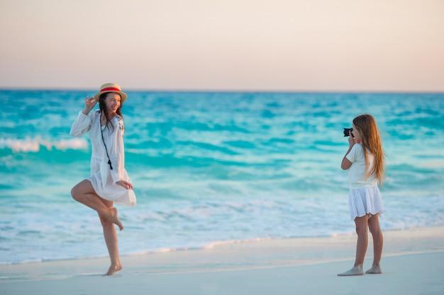 Piccola ragazza sveglia che prende foto della sua mamma alla spiaggia tropicale Foto Premium
